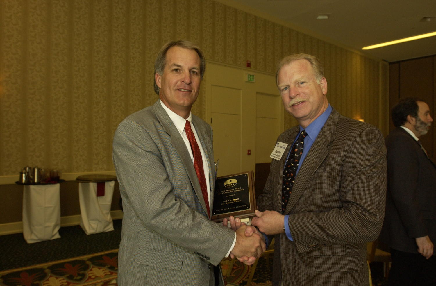 """[Donnie Baggett handing out plaque award to Bill Cornwell], Photograph of Donnis Bagget (right) handing an engraved plaque to Bill Cornwell, who is receiving the award from the 2004 Texas Daily News Association annual conference held in Corpus Christi. The plaque reads, """"2003 Mayborn Award for Community Leadership presented to Bill Cornwell, The Brazosport Facts. March 22, 2004 at Corpus Christi, Texas."""","""