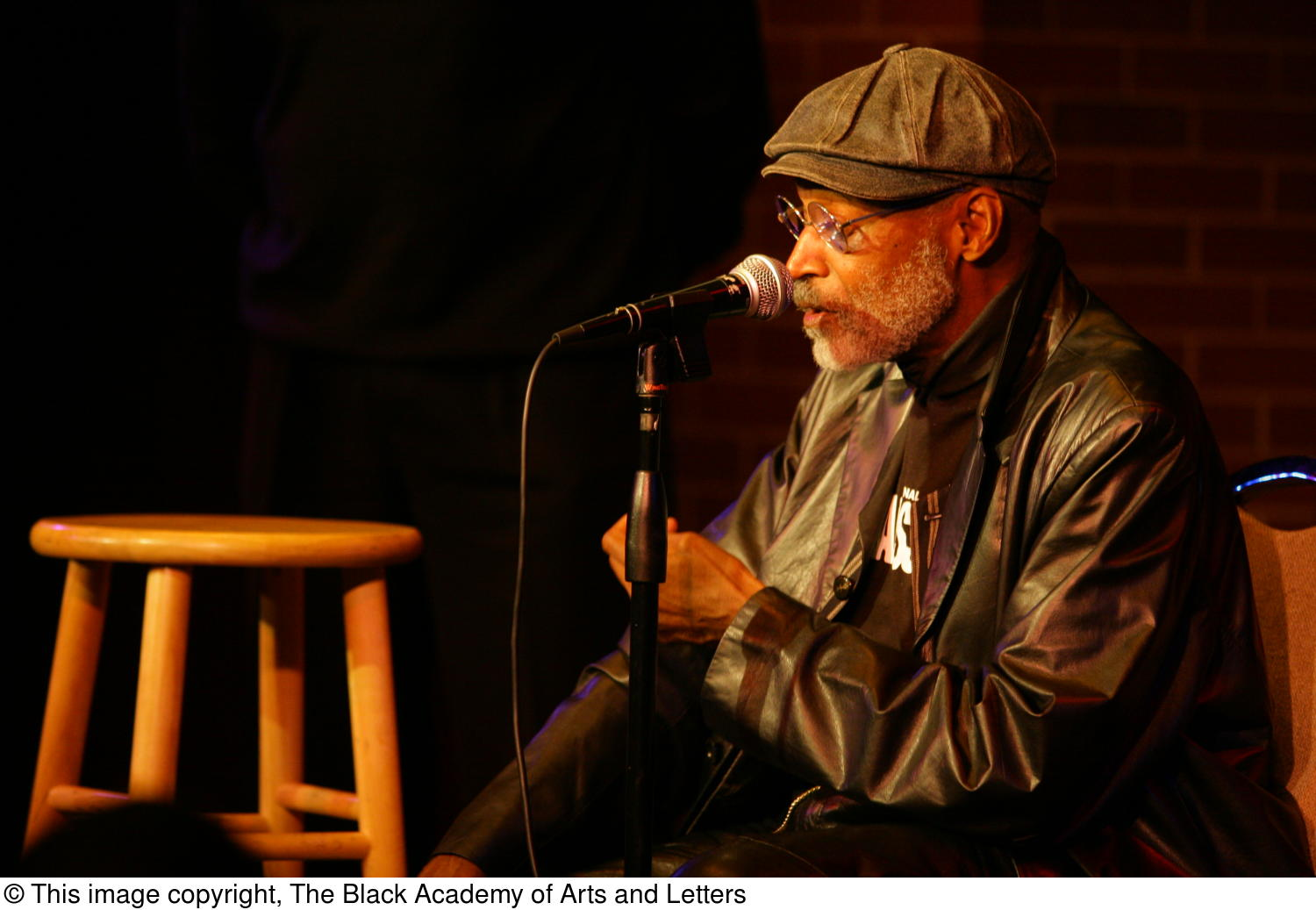 [Photograph of Melvin Van Peebles seated on stage at 24-Hour Film Feast]                                                                                                      [Sequence #]: 1 of 1