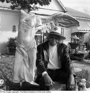 Black and white photograph of Willard Watson sitting outside, next to a large statue of an angel missing its arms and head.