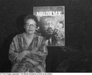 Black and white photograph of Laure Jean Lacy seated in front of a drawing of a man with the words Malcolm X above his head.