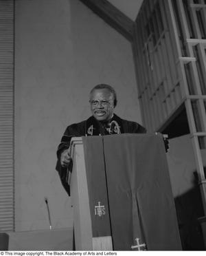 Black and white photograph of Rev. Marshall E. Hodge standing behind a podium. He wears black robes and a black sash.