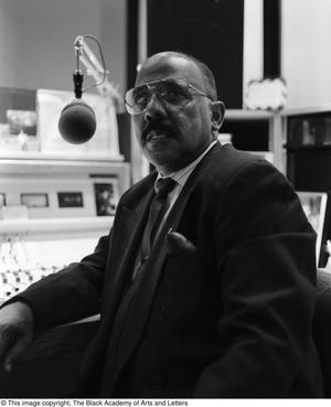 Black and white photograph of E. Joe Bagby sitting in front of a desk filled with control panels with a large microphone hanging near his head.