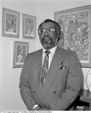 Black and white photograph of Abner Haynes standing in front of hung photographs of football players.
