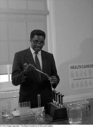 Black and white photograph of Dr. Jesse Jones in a lab. He holds a test tube and pipette, with other equipment on the table in front of him.