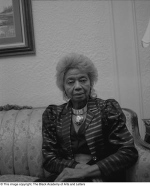 Black and white photograph of J'Lena Boykin seated on a couch.