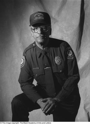 Black and white photograph of Lonnell E. Cooper, leaning arm on one raised knee. He wears a police officer uniform and cap.