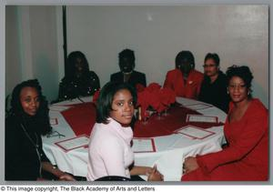 Primary view of object titled '[Guests seated at Christmas Kwanzaa soiree]'.