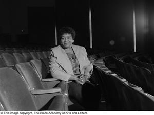 Black and white photograph of Versia L. Lacy sitting sideways in an auditorium seat.