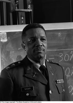 Black and white photograph of Col. Joe D. Sasser, wearing his military uniform, standing in front of a chalk board.
