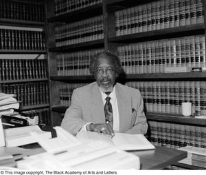 Black and white photograph of E. Brice Cunningham seated behind a desk coverd with open books. Two large books cases are completely full behind him.