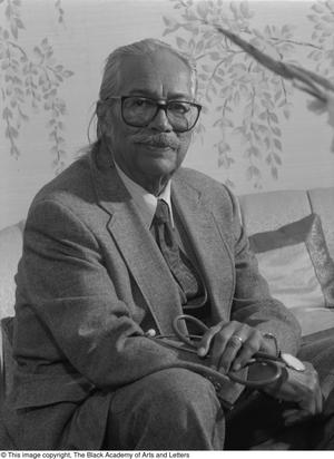 Black and white photograph of Dr. Marion J. Brooks seated on a couch. He holds a folded up stethescope in his hands.