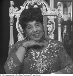 Black and white close up photograph of Mabel Meshach White seated in an ornate gold chair. She rests her chin on one raised hand.