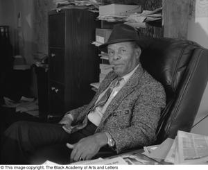 Black and white photograph of William Blair Jr. seated in an office with a cigar in his mouth. Newpspapers and boxes are seen on shevles and desks surounding him.
