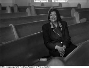 Black and white photograph of Dorothy N. Cole Davis seated in a pew of a church. Empty pews are visible all around her.
