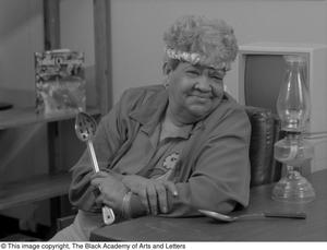 Black and white photograph of Clara Miles sitting at a table. She leans on the table and smiles, while holding a large metal slotted spoon in one hand.