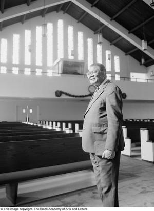 Black and white photograph of Rev. C.B.T. Smith standing in an empty church holding a book.