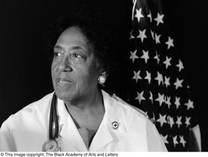 Black and white close up photograph of Lt. Mary E. Walton wearing a white coat, and a stethescope around her neck. An American flag is behind her.
