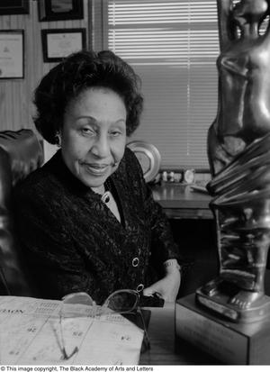 """Black and white photograph of Leona """"Tiny"""" Hawkins sitting behind a desk. She looks directily at the camera, and a large award statue sits on the desk to her right."""