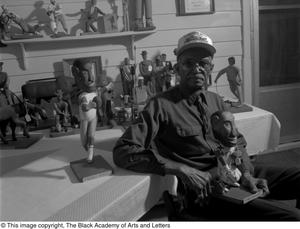 Black and white photograph of Deacon Eddie Moore seated. Small statues fill a table behind him, and he holds one in his lap.