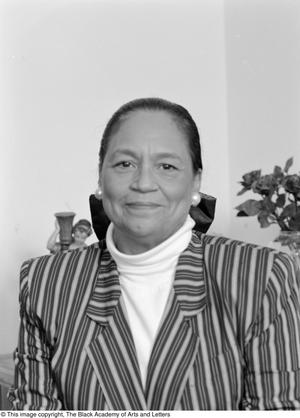 Black and white photograph of Rose White-Burke. She wears a striped blazer and white turtleneck.