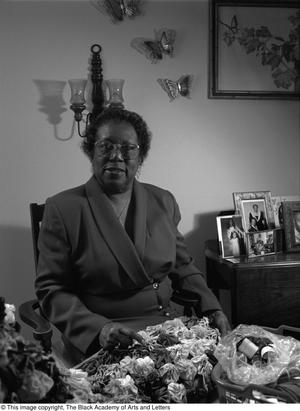 Black and white photograph of Althea Jones Hilliard seated, with a quilt and sewing basket in front of her.