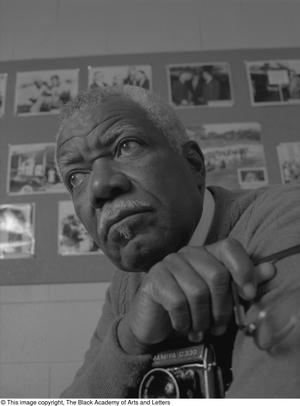 Black and white close up photograph of Marion Butts Sr. He holds a camera and a bulletin board full of photographs is visible behind him.