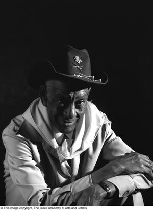 Black and white photograph of James Lazine in front of a black backdrop. He wears a black military stetson style hat, and a kerchief around his neck.