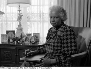 Black and white photograph of Lucy Phelps-Patterson seated in a chair. She holds a book on her lap, pen in hand. Framed photos stand on the table behind her.