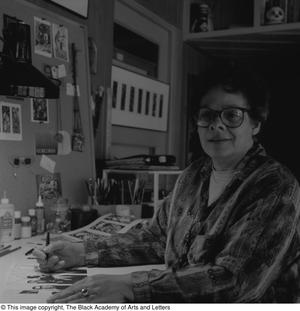 Black and white photograph of Laure Jean Lacy seated at a desk filled with crafting supplies. She holds a pen over a page, and looks at the camera.