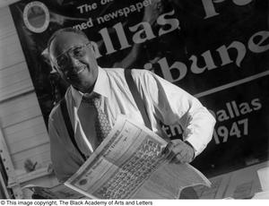Black and white photograph of Samuel Wicks holding open a newspaper. A large poster can be seen on the wall behind him, which reads Dallas Post Tribune.