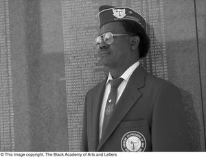 Black and white photograph of Willie Parker wearing garrison cap with an insignia and text that reads American Ex-Prisoner of War. His blazer and tie have the same insignia. He stands in front of a marble wall with names etched in it.