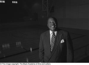 Black and white photograph of Robert Thomas standing in an empty basketball court. He wears a suit and tie.