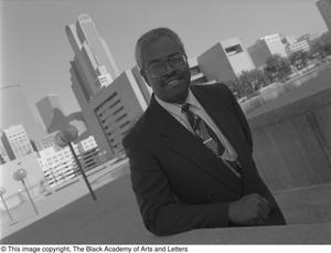 Black and white photograph of Fred L. Blair, out doors with the Dallas cityscape behind him.