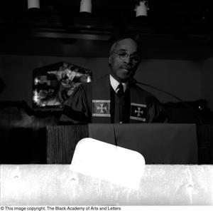 Black and white photograph of Rev. Zan W. Holmes Jr. standing behind a podium. He wears robes and a sash with crosses on either side of his chest.