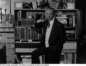 Black and white photograph of Lee G. Bilal standing in front of a bookcase. He wears a three piece suit.