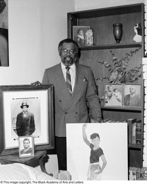 Primary view of object titled '[Abner Haynes posing with family portraits]'.