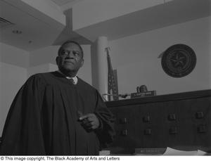 Black and white photograph of Judge L. Clifford Davis standing in a courtroom in front of the judge's desk. He wears a black robe.