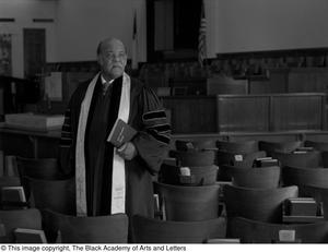 Photograph of Rev. J.D. Mooring standing in a row of theater style seats. He wears dark robes and holds a copy of the New Testament in his hand.