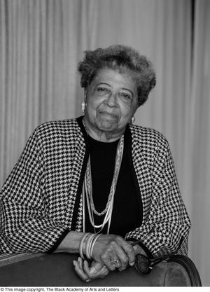 Black and white photograph of Fannie C. Smith standing behind a chair, leaning on its back with her arms, hands clasped.