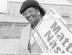 Black and white photgraph of Mattie Nash, outdoors holding a sign that reads Mattie Nash for City Council.