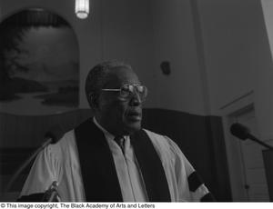 Black and white photograph of Rev. Louie Belvet George standing behind a podium, wearing white robes.