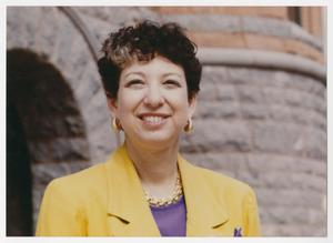 A woman with short brown hair stands in front of a brick structure. She wears gold earrings and a gold necklace. She also has on a bright yellow blazer with a purple shirt underneath.