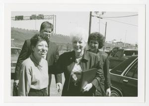 Black and white photo of three women with short hair, and a man behind them. They are standing by a road with cars driving by.