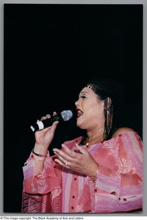 Primary view of object titled '[Angela Bofill singing with her left hand up]'.