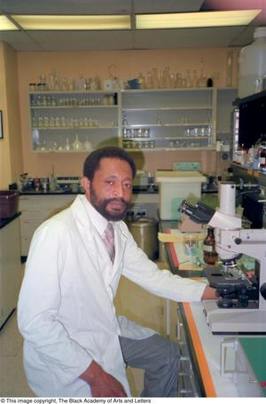 Color photograph of Dr. Edison Fowlks sitting on a stool in a biology lab. He wears a white lab coat and sits before a microscope. Containers and other equipment can be seen around him.