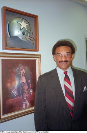 Color photograph of Pettis Norman standing next to a framed football helmet with a white star, and a framed photo of a football player on a field carrying two helmets.