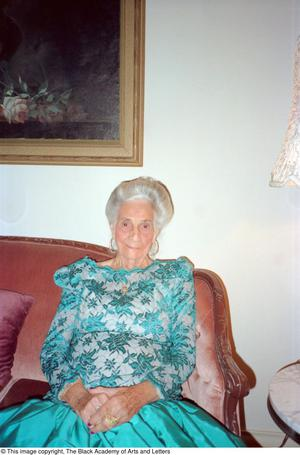Color photograph of Pearl C. Anderson sitting at one end of a couch. She wears a teal skirt and top with teal embroiderd floral pattern.