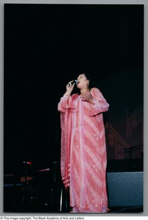 Primary view of object titled '[Full body shot of Angela Bofill singing onstage in a pink dress]'.