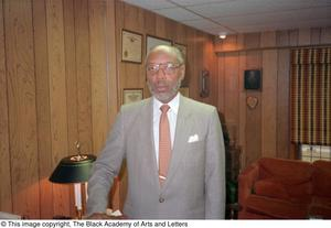 Color photograph of Louise A. Bedford standing in an office. Behind him are framed documents hanging on the wall, and a couch to the right.