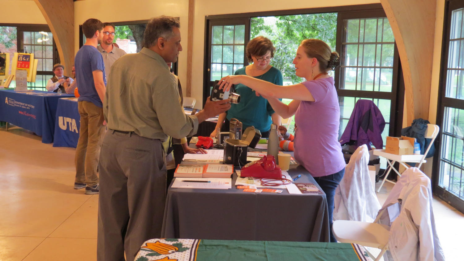 [Visitors looking at camera], Photograph of visitors looking at old cameras at the Sixth Floor Museums booth table during the DFW Archives Bazaar at the Dallas Heritage Village Pavilion. Stephanie Allen-Givens is helping them and Lindsey Richardson is further back.,